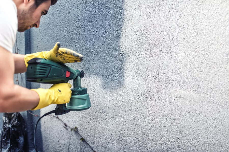 Photo close up of a man spray painting an external wall