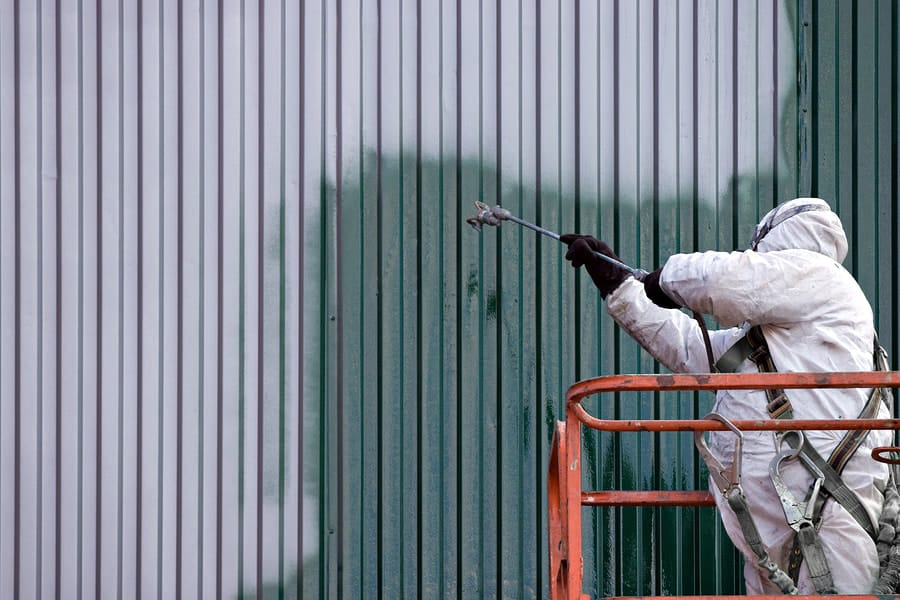 Photo of a man spraying an industrial factory
