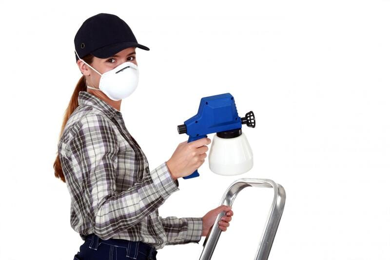 Photo of a woman holding a spray gun whilst stood on a ladder and wearing a protective mask